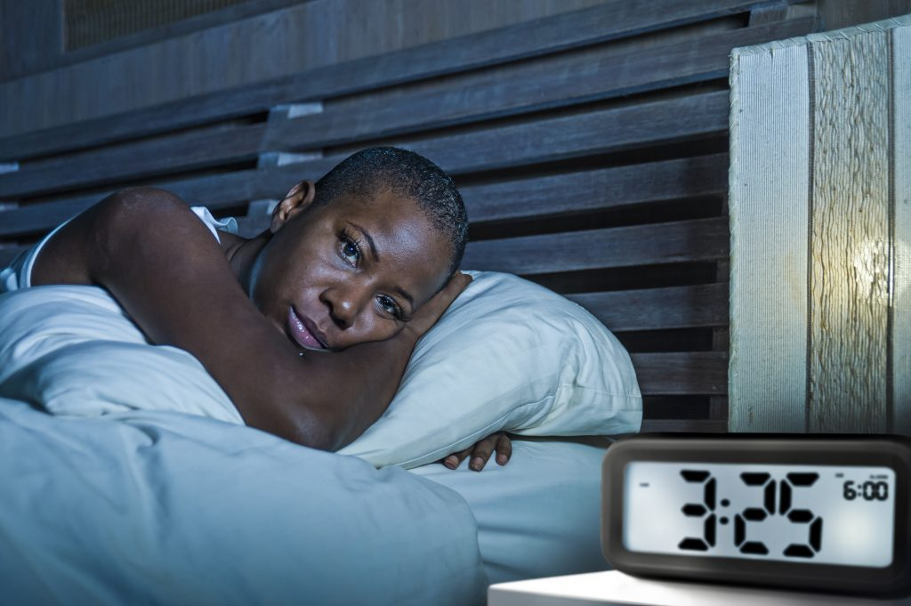 lifestyle portrait of young sad and depressed black afro American woman awake on bed sleepless suffering insomnia sleeping disorder and anxiety problem with alarm clock late night hour